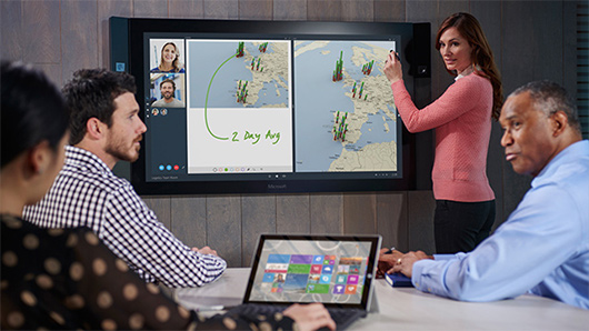 Woman using pinch and zoom on Microsoft Surface Hub screen while two men watch