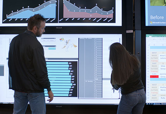 A man and woman collaborating with a group of Microsoft Surface Hub devices.