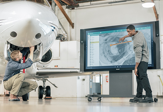 One man working on plane and one man using touchscreen on Microsoft Surface Hub