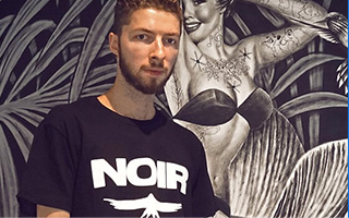 Artist Noir looks into camera with intricate illustrations  behind him