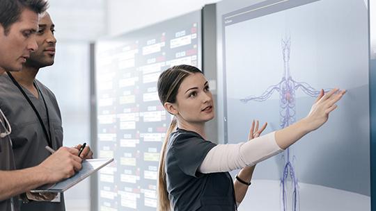 Woman using touchscreen on Surface Hub and two men taking notes