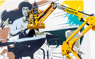 Artist Odeith standing on a hydraulic crane painting a large mural