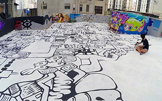 Artist Bao sits cross-legged on a roof terrace surrounded by a massive floor mural spanning the entire floor around her