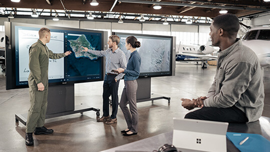Two men using touchscreen of Microsoft Surface Hub while man and woman watch