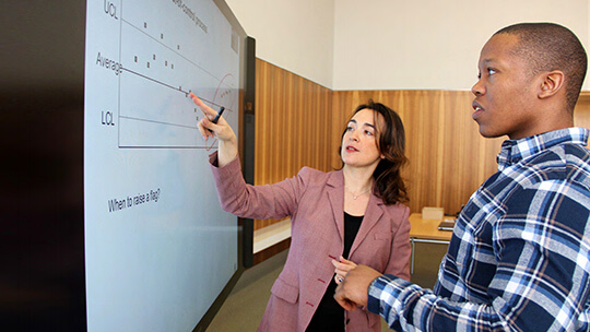Woman using touchscreen on Microsoft Surface Hub while man watches