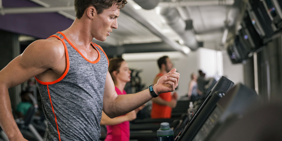 A man looks at Microsoft Band in his wrist while working out in a gym.
