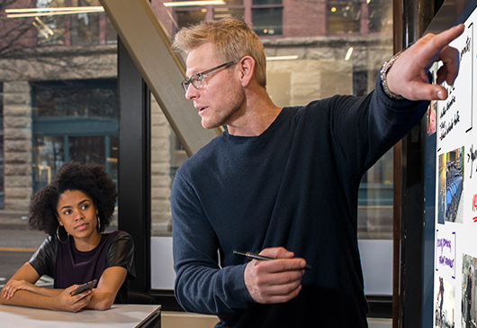 Man using touchscreen on Microsoft Surface Hub and two women watching